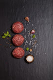 Raw ground beef meat steak cutlets with herbs and spices on blac. K table or board for background. Selective focus Royalty Free Stock Images