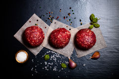 Raw ground beef meat steak cutlets with herbs and spices on blac. K table or board for background. Selective focus. Toned Royalty Free Stock Photos