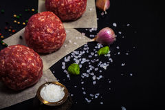 Raw ground beef meat steak cutlets with herbs and spices on blac. K table or board for background. Sharpness on the salt shaker. Toned Royalty Free Stock Photo