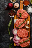 Raw ground beef meat steak cutlets with herbs and spices. Raw ground beef meat steak cutlets with herbs and spices on dsrk background Royalty Free Stock Photos