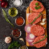 Raw ground beef meat steak cutlets with herbs and spices. Raw ground beef meat steak cutlets with herbs and spices on dsrk background Stock Photos