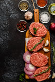 Raw ground beef meat steak cutlets with herbs and spices. Raw ground beef meat steak cutlets with herbs and spices on dsrk background Stock Images