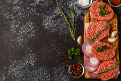Raw ground beef meat steak cutlets with herbs and spices. Raw ground beef meat steak cutlets with herbs and spices on dsrk background Stock Image