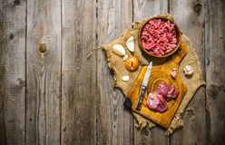 Raw ground beef. Prepatared of meat. The preparation of minced meat and onions on the old fabric. On a wooden table. Free space for text . Top view Stock Photos