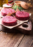 Raw ground beef, round patties for making burgers. Organic raw ground beef, round patties for making homemade burger on wooden cutting board Stock Image