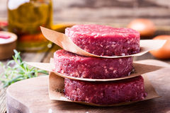 Raw ground beef, round patties for making burgers. Organic raw ground beef, round patties for making homemade burger on wooden cutting board Stock Images