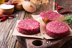 Raw ground beef, round patties for making burgers. Organic raw ground beef, round patties for making homemade burger on wooden cutting board Stock Photos