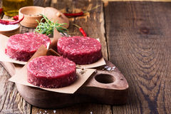 Raw ground beef, round patties for making burgers. Organic raw ground beef, round patties for making homemade burger on wooden cutting board Royalty Free Stock Photography