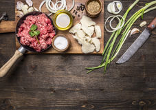 Raw ground beef in a small frying pan, on a chopping board with onions, bread, butter and spices wooden rustic background top v Stock Photos