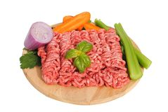 Raw ground beef with vegetables. On wooden cutting board Stock Photo