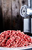 Raw ground beef on a white plate with meat grinder. Pinky raw ground beef on a white plate with meat grinder near it. Ground beef can be used to cook hamburgers Stock Photo
