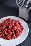 Raw ground beef on a white plate with meat grinder Royalty Free Stock Photos
