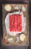 Raw ground beef on  wooden table with Spices and onion. Top view Stock Images