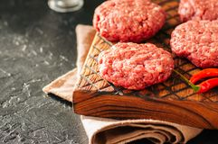 Raw ground meat beef burgers on a wooden board. Close up and cop. Y space Stock Photography