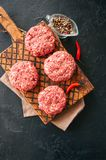 Raw ground meat beef burgers on a wooden board. Top view Stock Photos