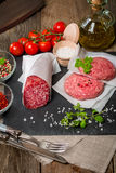 Raw Ground meat Burger and salami. With seasonings, tomato and olive oil on slate background Stock Photos