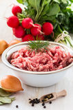 Raw ground meat. In white bowl. Minced pork on a background of fresh organic vegetables Royalty Free Stock Photo
