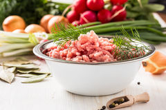Raw ground meat. In white bowl. Minced pork on a background of fresh organic vegetables Stock Photos