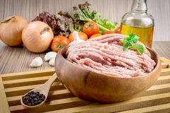 Raw ground meat in wood bowl. Minced pork on a background of fresh organic vegetables Stock Photo
