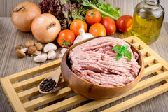 Raw ground meat in wood bowl. Minced pork on a background of fresh organic vegetables Stock Photos
