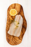 Raw haddock with dill and lemon on a wooden board. Raw haddock with dill and slice lemon on a wooden board Royalty Free Stock Photography