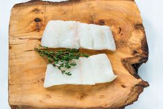 Raw haddock fillets - top view. Raw haddock fillets on wooden board - top view Stock Image
