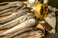 Raw hake with bay leaffrom kitchen knife, olive oil and lemon. Raw hake with bay leafon plastic tray from kitchen knife, olive oil and lemon Royalty Free Stock Image