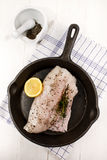 Raw hake fillet with thyme and a lemon slice. Raw hake fillet with thyme, crushed peppercorn and a lemon slice in a cast iron pan Stock Photo