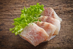 Raw hake fish fillet pieces. On dark wooden table Royalty Free Stock Photo
