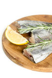 Raw hake fish with lemon and rosemary branches on the wooden board.  Royalty Free Stock Photos