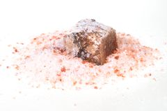 Raw Halite mineral in pile of pink Himalayan Salt. Raw Halite mineral in pile of grained pink Himalayan Salt on white background royalty free stock photos