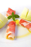 Raw ham and yellow melon. A dish with raw ham, yellow melon and olive oil garnish Royalty Free Stock Images