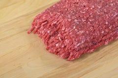 Raw hamburger on butcher block Stock Photography
