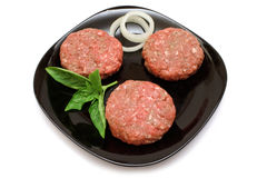 Raw Hamburger Patties. On a black plate with onion rings and Basil garnish, isolated on white with clipping path Stock Photography