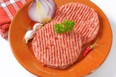 Raw hamburger patties Stock Images