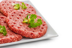 Raw hamburger slices on white plate Stock Photography