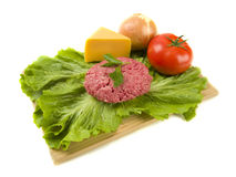 Raw hamburger with toppings Royalty Free Stock Photos