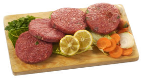 Raw hamburgers. Four raw hamburger on a cutting board isolated on white Royalty Free Stock Image