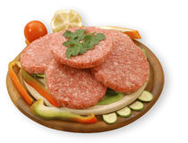 Raw hamburgers. Four raw hamburgers on a cutting board, isolated, with clipping path Stock Image