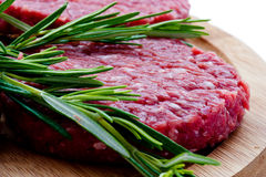 Raw hamburgers with cellophane and rosemary on wooden board Stock Photography