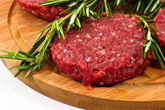 Raw hamburgers with cellophane and rosemary on wooden board Royalty Free Stock Photo