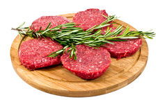 Raw hamburgers with cellophane and rosemary on wooden board Royalty Free Stock Photography