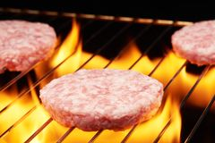Raw hamburgers on grill with flame. Raw hamburgers cooking on grill with flame Royalty Free Stock Photo