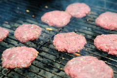 Raw Hamburgers On The Grill. Uncooked hamburger patties just tossed on the barbecue grill to start cooking Royalty Free Stock Images