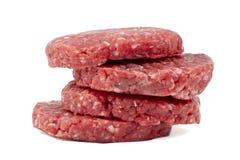 Raw hamburgers with transparent protective film. Raw hamburgers with protective film in white background Stock Image