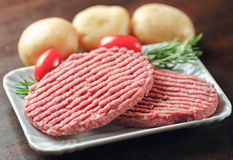 Raw hamburgers on wooden table Royalty Free Stock Photography