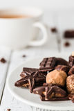 Raw handmade chocolate candies, cup of tea on white wooden background Royalty Free Stock Image