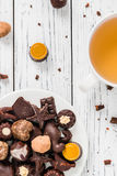 Raw handmade chocolate candies, cup of tea on white wooden background Stock Photography