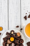 Raw handmade chocolate candies, cup of tea on white wooden background Royalty Free Stock Images