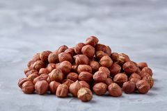 Raw hazelnut on heap isolated on white background, selective focus, shallow depth of field. Raw hazelnut on heap isolated on white textured background, close-up royalty free stock photo